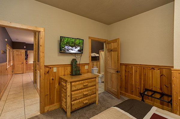Queen bedroom with a dresser, tv, and en suite Corthouse, a 4-bedroom cabin rental located in Pigeon Forge