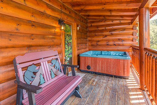 Custom bear bench and a hot tub on a covered deck at Lazy Bear Lodge, a 2 bedroom cabin rental located in Pigeon Forge