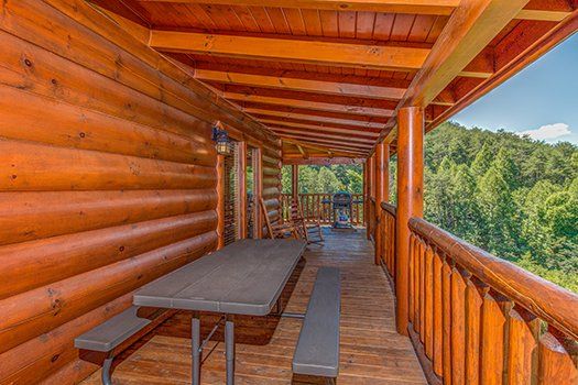 Picnic table on the covered deck at Lazy Bear Lodge, a 2 bedroom cabin rental located in Pigeon Forge