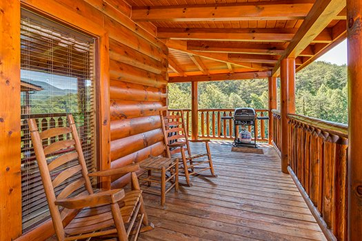 Two rocking chairs and a grill on the covered deck at Lazy Bear Lodge, a 2 bedroom cabin rental located in Pigeon Forge