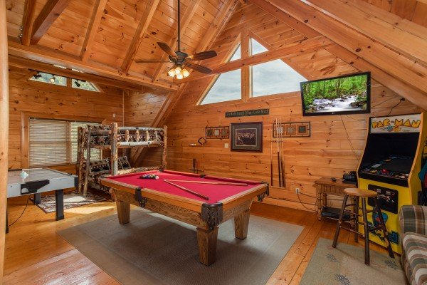 Bunk bed, air hockey, pool, and arcade game in the loft at Lazy Bear Lodge, a 2 bedroom cabin rental located in Pigeon Forge
