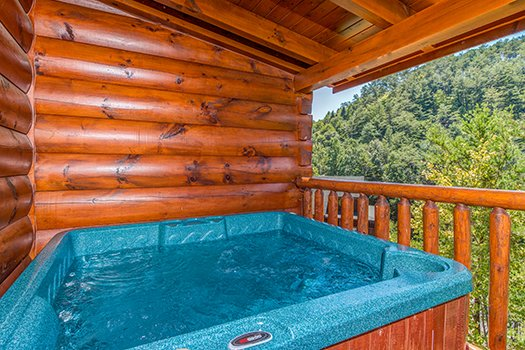 Hot tub on a covered deck and wooded views at Lazy Bear Lodge, a 2 bedroom cabin rental located in Pigeon Forge