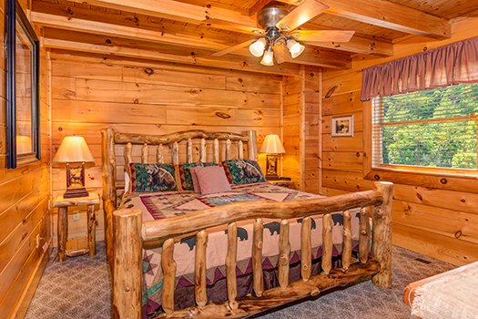 Bedroom with a king log bed and two night stands at Lazy Bear Lodge, a 2 bedroom cabin rental located in Pigeon Forge