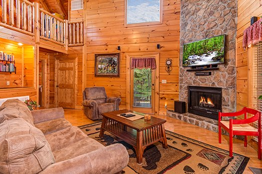 Living room with a fireplace and TV at Lazy Bear Lodge, a 2 bedroom cabin rental located in Pigeon Forge