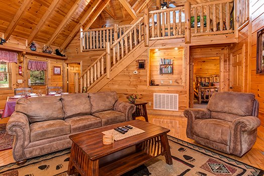 Living room with the loft area behind at Lazy Bear Lodge, a 2 bedroom cabin rental located in Pigeon Forge