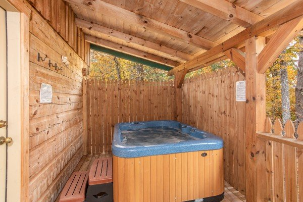 Hot tub on a covered porch with a privacy fence at All Shook Up, a 1 bedroom cabin rental located in Pigeon Forge
