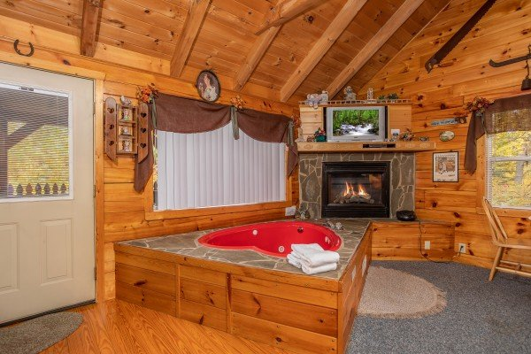 Jacuzzi and fireplace in a studio setting All Shook Up, a 1 bedroom cabin rental located in Pigeon Forge