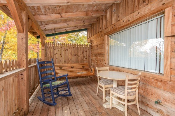 Outdoor seating with a porch swing rocking chair and dining space for two at All Shook Up, a 1 bedroom cabin rental located in Pigeon Forge