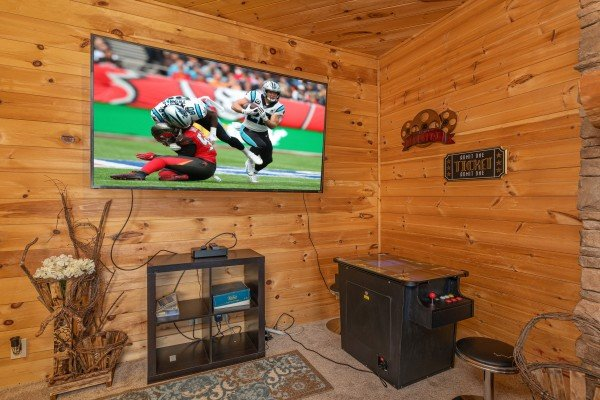 Large TV and arcade game at Heavenly Homestead, a 4 bedroom cabin rental located in Pigeon Forge