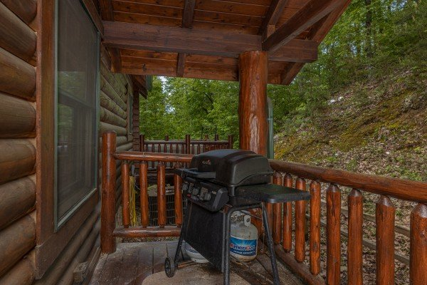 Gas grill on a covered deck at Heavenly Homestead, a 4 bedroom cabin rental located in Pigeon Forge