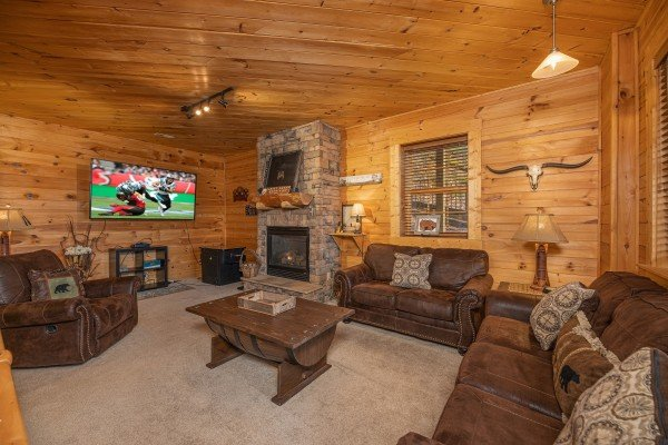 TV and fireplace in a lower living room at Heavenly Homestead, a 4 bedroom cabin rental located in Pigeon Forge