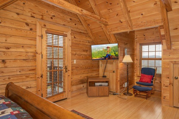 TV and glider in a bedroom with deck access at Heavenly Homestead, a 4 bedroom cabin rental located in Pigeon Forge