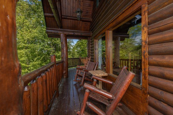 Rocking chairs on a covered deck at Heavenly Homestead, a 4 bedroom cabin rental located in Pigeon Forge