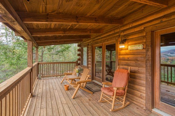 Covered deck with Adirondack bench and rocking chair at Enchanted Evening, a 1-bedroom cabin rental located in Pigeon Forge