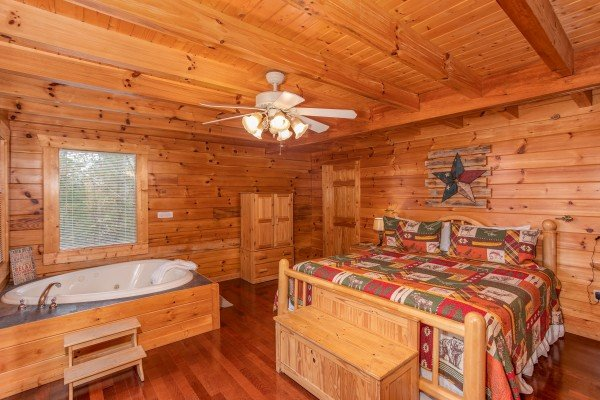 First king-sized bedroom with heart-shaped jacuzzi tub at Enchanted Evening, a 1-bedroom cabin rental located in Pigeon Forge
