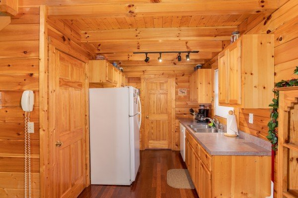 Galley kitchen with white appliances at Enchanted Evening, a 1-bedroom cabin rental located in Pigeon Forge