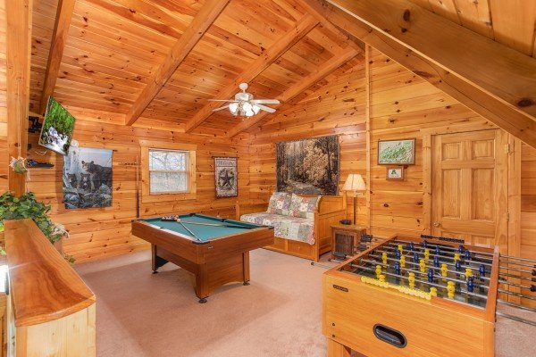 Pool table, foosball table, TV, and trundle bed in the loft space at Enchanted Evening, a 1-bedroom cabin rental located in Pigeon Forge