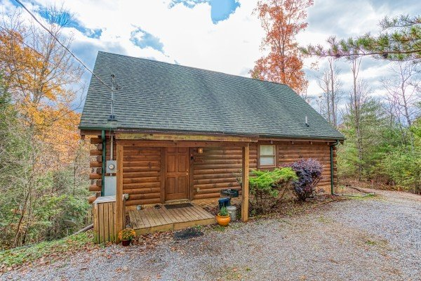 Looking at the cabin from the gravel parking at Enchanted Evening, a 1-bedroom cabin rental located in Pigeon Forge