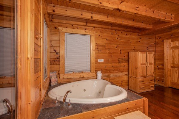 Heart-shaped jacuzzi in the bedroom at Enchanted Evening, a 1-bedroom cabin rental located in Pigeon Forge