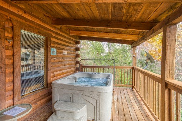 Hot tub on a covered deck at Enchanted Evening, a 1-bedroom cabin rental located in Pigeon Forge
