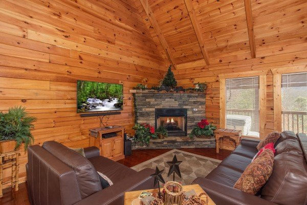 Fireplace, TV, and king sleeper sofa in the living room at Enchanted Evening, a 1 bedroom Pigeon Forge cabin rental