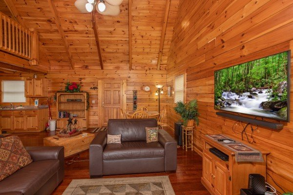 Oversized chair, king sleeper sofa, and large TV in the living room at Enchanted Evening, a 1 bedroom Pigeon Forge cabin rental