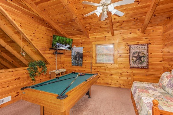 Trundle bed, pool table, and TV in the loft space at Enchanted Evening, a 1-bedroom cabin rental located in Pigeon Forge