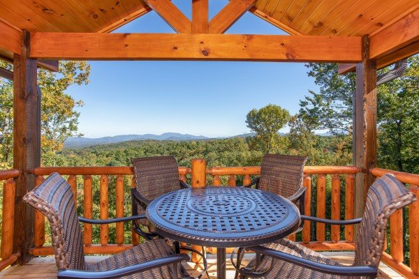 Dining table for four on the covered deck at Panorama, a 2 bedroom cabin rental located in Pigeon Forge
