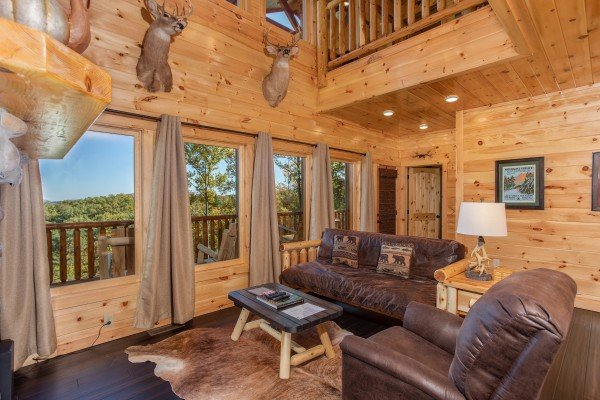 Living room with high ceiling and large windows at Panorama, a 2 bedroom cabin rental located in Pigeon Forge
