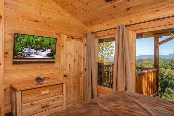 TV and dresser in a bedroom at Panorama, a 2 bedroom cabin rental located in Pigeon Forge
