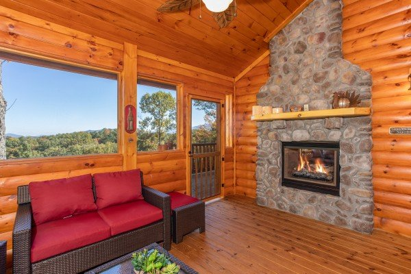 Fireplace on the screened in porch at Panorama, a 2 bedroom cabin rental located in Pigeon Forge