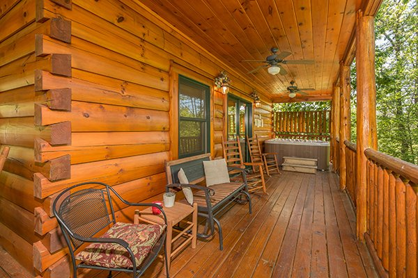 Back deck with a chair, bench, and rockers at Bearfoot Paradise, a 3-bedroom cabin rental located in Pigeon Forge