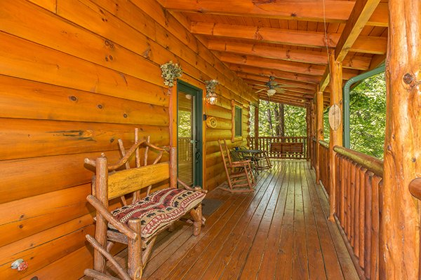 Bench and rockers on the covered deck at Bearfoot Paradise, a 3-bedroom cabin rental located in Pigeon Forge