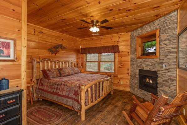 Bedroom on the lower level with a king log bed, fireplace, and TV at Bearfoot Paradise, a 3 bedroom cabin rental in Pigeon Forge