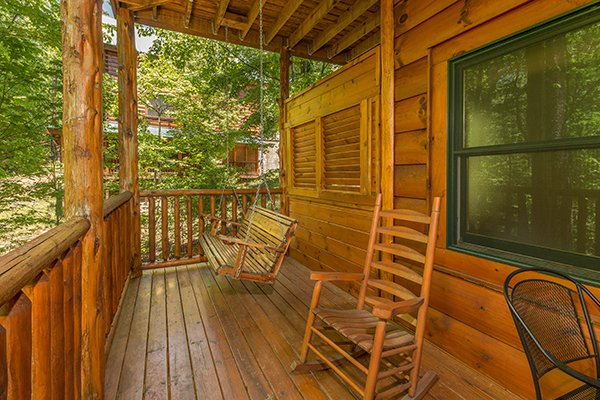 Deck with a porch swing and rocking chair at Bearfoot Paradise, a 3-bedroom cabin rental located in Pigeon Forge