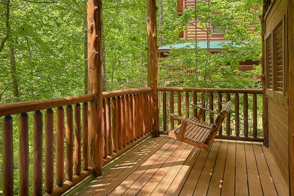 Porch swing on the deck at Bearfoot Paradise, a 3-bedroom cabin rental located in Pigeon Forge