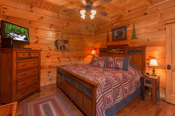 Bedroom with a king-sized bed, dresser, and television at Bearfoot Paradise, a 3-bedroom cabin rental located in Pigeon Forge