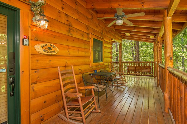 Front deck with rockers and bistro set at Bearfoot Paradise, a 3-bedroom cabin rental located in Pigeon Forge