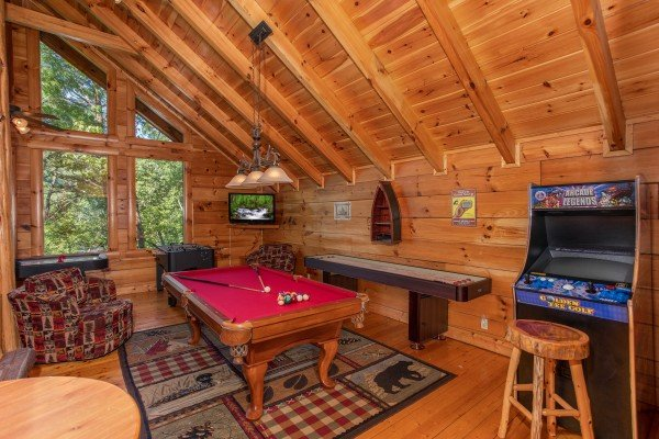 Red felted pool table, shuffleboard table, and arcade game at Bearfoot Paradise, a 3-bedroom cabin rental located in Pigeon Forge
