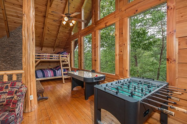 Bunks and foosball table and air hockey table at Bearfoot Paradise, a 3-bedroom cabin rental located in Pigeon Forge