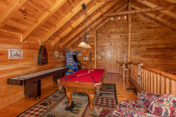 Red felted pool table, shuffleboard game, and arcade game in the game loft at Bearfoot Paradise, a 3-bedroom cabin rental located in Pigeon Forge