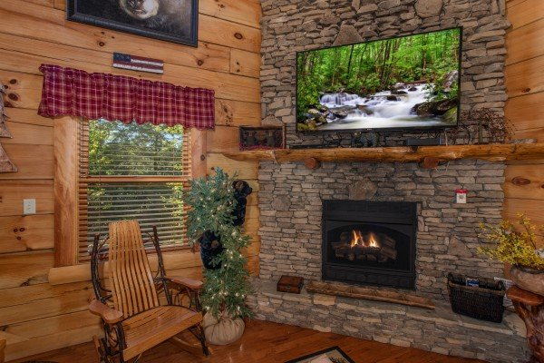 Rocker next to a fireplace with a television at Bearfoot Paradise, a 3-bedroom cabin rental located in Pigeon Forge