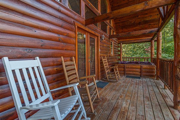 Rocking chairs and a hot tub on the covered porch at Lincoln Logs, a 2 bedroom cabin rental located in Gatlinburg