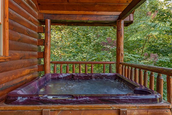 Hot tub on the covered porch at Lincoln Logs, a 2 bedroom cabin rental located in Gatlinburg