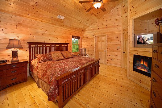 Fireplace in bedroom with king-sized bed at Cozy Creek, a 3-bedroom cabin rental located in Pigeon Forge