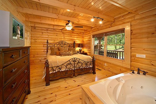 King-sized bed and jacuzzi tub in main floor bedroom at Cozy Creek, a 3-bedroom cabin rental located in Pigeon Forge