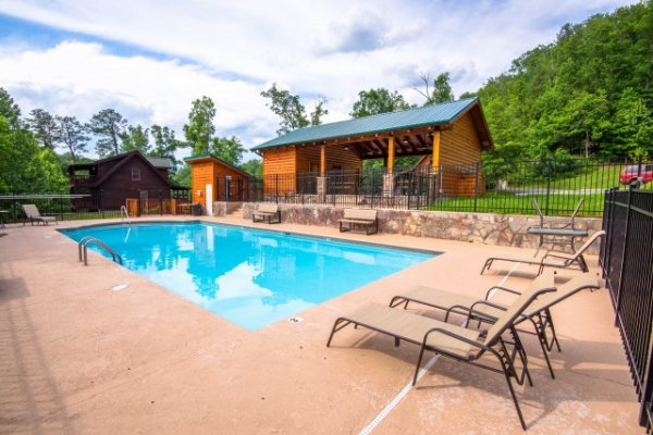 Outdoor resort pool with chaise lounge chairs at Cozy Creek, a 3-bedroom cabin rental located in Pigeon Forge