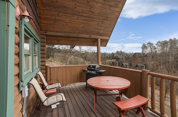 Covered deck with a propane grill, two chairs, and a dining table at Hanky Panky, a 1-bedroom cabin rental located in Pigeon Forge