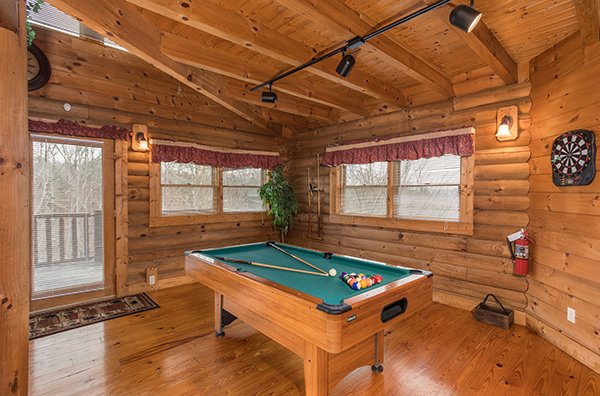 Pool table and dart board in the game room at Hanky Panky, a 1-bedroom cabin rental located in Pigeon Forge