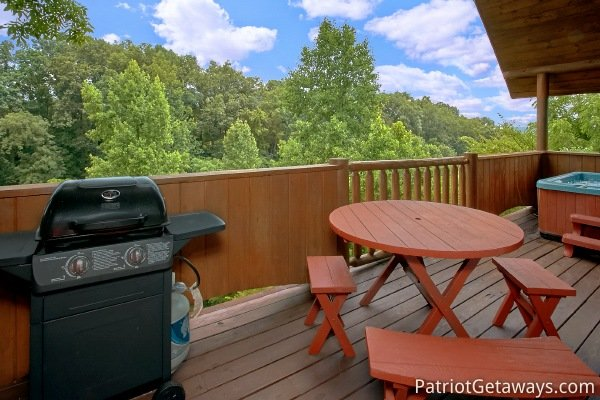 Propane grill and dining table on the covered deck at Hanky Panky, a 1-bedroom cabin rental located in Pigeon Forge